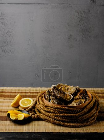 Photo for Raw fresh oysters with lemon slices, view with copy space - Royalty Free Image