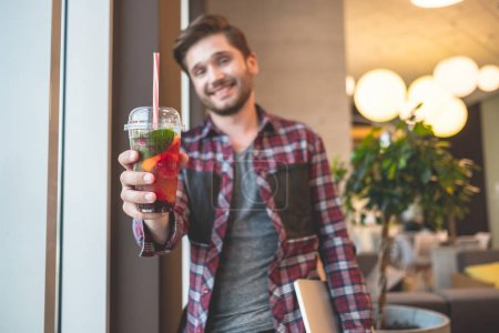 portrait of young bearded man in plaid shirt holding fresh drink and laptop indoor on background