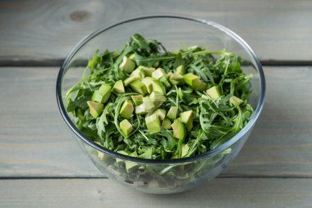 Photo for Close-up photo of healthy fresh green salad with avocado and arugula in glass bowl on table - Royalty Free Image