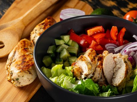 Photo for Fresh diet healthy salad with grilled chicken and organic vegetables on black background, flat lay view for copy space text menu and recipe - Royalty Free Image
