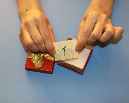 Photo pour Mains tenant une boîte-cadeau rouge avec un arc doré brillant dans laquelle le billet est le numéro un - image libre de droit
