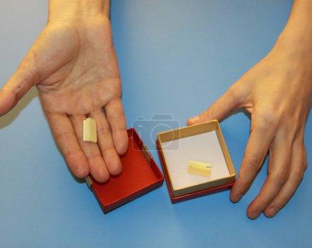 Photo pour Les mains de la Saint-Valentin tenant une boîte-cadeau rouge avec un arc doré et brillant dans laquelle une note de déclaration d'amour, de surprise - image libre de droit