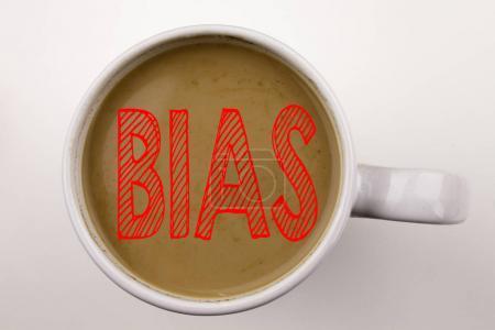 Photo pour Mot, écrit le texte de partialité dans le café dans la tasse. Concept d'affaires pour préjudice biaisées un traitement injuste sur fond blanc. Texte en noir avec le mot rouge. - image libre de droit