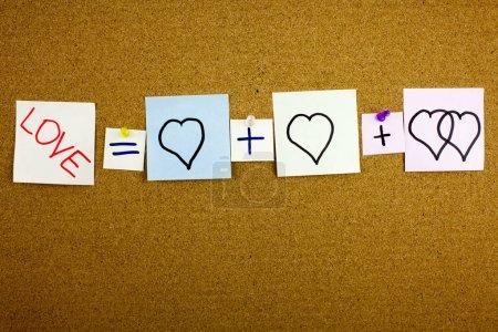 Une note jaune collante post-it écriture, légende, inscription équation amour ou romantique concept de relation présenté comme équation mathématique avec des c?urs, notes collantes colorées, en ext noir sur un bâton