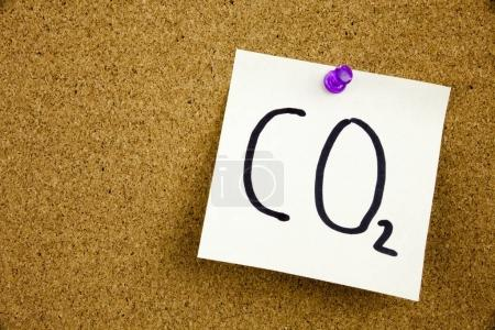 Une note jaune collante écriture, légende, inscription Phrase CO2 en ext noir sur une note collante épinglée sur un panneau d'affichage en liège