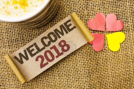 Writing note showing  Welcome 2018. Business photo showcasing Celebration New Celebrate Future Wishes Gratifying Wish written on sticky Note on the jute background Love Hearts next to it.