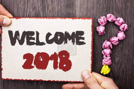 Word writing text Welcome 2018. Business concept for Celebration New Celebrate Future Wishes Gratifying Wish written on Cardboard Piece Holding By Hand on wooden background Question Mark.