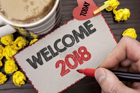 Writing note showing  Welcome 2018. Business photo showcasing Celebration New Celebrate Future Wishes Gratifying Wish written Man Holding Marker on Cardboard wooden background Today Coffee.