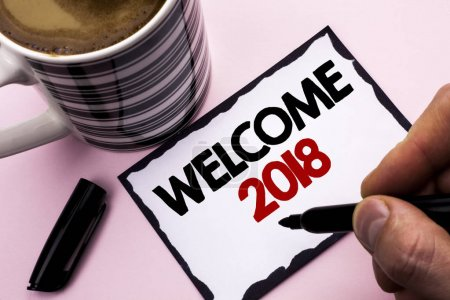 Handwriting text writing Welcome 2018. Concept meaning Celebration New Celebrate Future Wishes Gratifying Wish written by Man on Sticky Note paper holding Marker plain background Coffee Cup