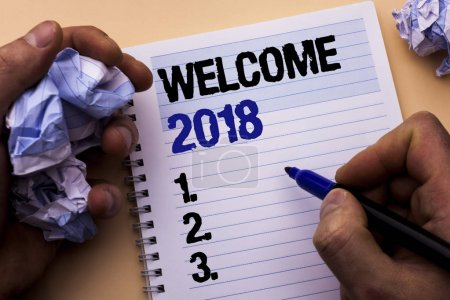 Handwriting text Welcome 2018. Concept meaning Celebration New Celebrate Future Wishes Gratifying Wish written by Man on Notebook Book Holding Marker on the plain background.