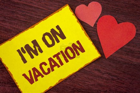 Conceptual hand writing showing I Am im On Vacation. Business photo text Break from stressful work pressure travel worldwide written on Yellow Sticky note paper on wooden background Hearts.