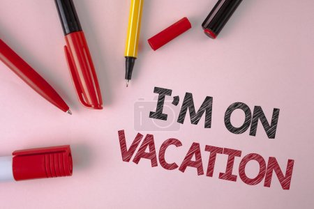 Conceptual hand writing showing I Am im On Vacation. Business photo text Break from stressful work pressure travel worldwide written on plain Pink background Pens and Marker next to it.