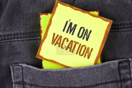 Handwriting text writing I Am im On Vacation. Concept meaning Break from stressful work pressure travel worldwide written on Sticky Note Paper placed on the Jeans background.