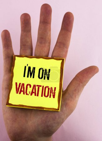 Text sign showing I Am im On Vacation. Conceptual photo Break from stressful work pressure travel worldwide written on Yellow Sticky Note Paper placed on the Hand on the plain background.