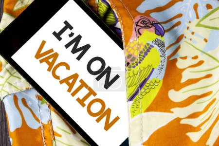 Conceptual hand writing showing I Am im On Vacation. Business photo text Break from stressful work pressure travel worldwide written on Mobile Phone Screen on the printed fabric background.