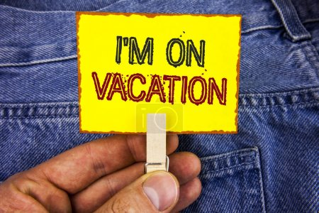 Word writing text I Am im On Vacation. Business concept for Break from stressful work pressure travel worldwide written on Yellow Sticky Note Paper holding by man with Clip on Jeans background