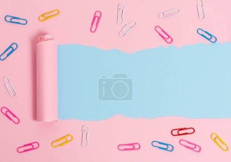 Zerrissene Pappe mit Büroklammer, die über einem weichen Farbtisch platziert ist. Dickes zerrissenes Papier und Papeterie auf pastellfarbenem Hintergrund. Künstlerische Art und Weise der Anordnung flacher Lagen-Fotografie