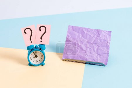 Photo for Mini size alarm clock beside a Paper sheet placed tilted on pastel backdrop - Royalty Free Image