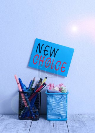 Photo for Text sign showing New Choice. Business photo text having lot of options and adding another one to choose between Blue Sticky Card on Wall Two Pencil Pots Pens Pencils Markers Waste Paper - Royalty Free Image