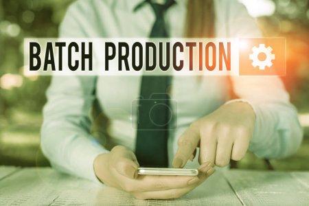 Foto de Conceptual hand writing showing Batch Production. Concepto que significa que los productos se analizan en grupos llamados lote Femenino hombre de negocios sentado y teniendo teléfono móvil. - Imagen libre de derechos