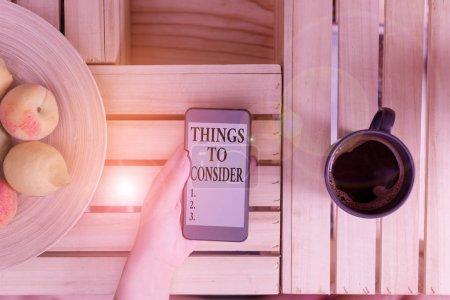Escritura manual conceptual que muestra las cosas a considerar. Lista de presentación de fotos de negocios para comprobarlo o hacerlo Horario de compras Mujer de mesa de tiempo con teléfono inteligente portátil y tecnología de suministros de oficina .
