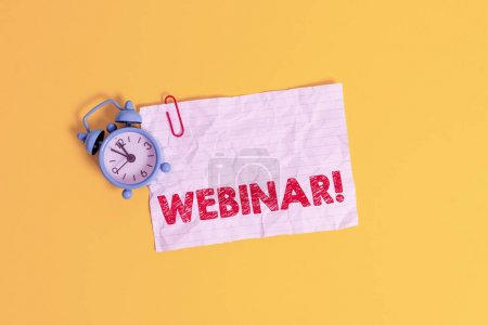Photo for Text sign showing Webinar. Business photo showcasing a seminar or other presentation that takes place on the Internet Metal alarm clock clip blank crushed note sheet colored background - Royalty Free Image
