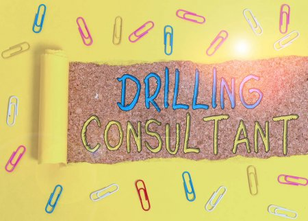 Photo for Text sign showing Drilling Consultant. Business photo text onsite supervision of daytoday drilling operations Paper clip and torn cardboard placed above a wooden classic table backdrop - Royalty Free Image
