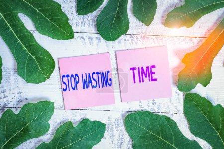 Photo pour Word writing text Stop Wasting Time. Photographie d'entreprise conseillant de faire une démonstration ou de commencer à planifier et à utiliser judicieusement Dépliant entourant un bloc-notes au-dessus d'une table classique en bois comme arrière-plan - image libre de droit