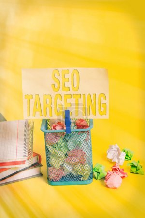 Writing note showing Seo Targeting. Business photo showcasing Specific Keywords for Location Landing Page Top Domain Trash bin crumpled paper clothespin office supplies yellow.