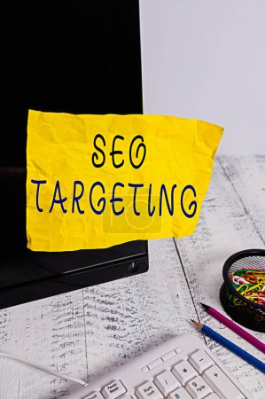 Text sign showing Seo Targeting. Conceptual photo Specific Keywords for Location Landing Page Top Domain Note paper taped to black computer screen near keyboard and stationary.