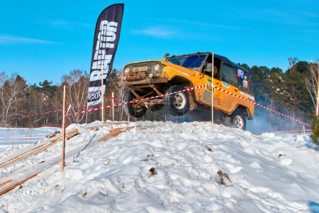 TOMSK, RUSSIA - FEBRUARY 17, 2018: Winter auto show of jeeps - ring race with obstacles, off-road trial. Jumping from jeeps. Yellow jeep in jump from a springboard. Offroad concept.