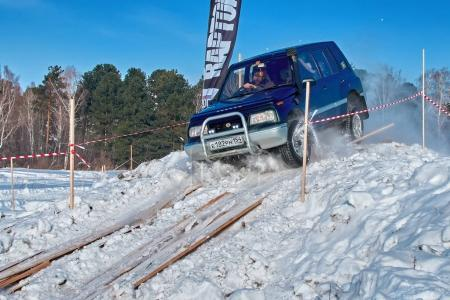 TOMSK, RUSSIA - FEBRUARY 17, 2018: Winter auto show of jeeps - ring race with obstacles, off-road trial. Jumping from jeeps. Suzuki Grand Vitara in jump from springboard. Offroad concept.