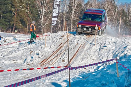 TOMSK, RUSSIA - FEBRUARY 17, 2018: Winter auto show of jeeps - ring race with obstacles, off-road trial. Jumping from jeeps. Land Rover Discovery in jump from springboard. Offroad concept.