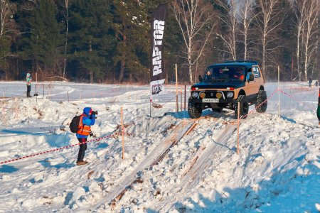 TOMSK, RUSSIA - FEBRUARY 17, 2018: Winter auto show of jeeps - ring race with obstacles, off-road trial. Jumping from jeeps. Offroad concept.