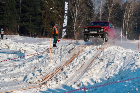 TOMSK, RUSSIA - FEBRUARY 17, 2018: Winter auto show of jeeps - ring race with obstacles, off-road trial. Jumping from jeeps. Red car in jump from springboard. Offroad concept.