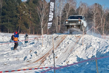 TOMSK, RUSSIA - FEBRUARY 17, 2018: Winter auto show of jeeps - ring race with obstacles, off-road trial. Jumping from jeeps. White car in high jump from springboard. Offroad concept.