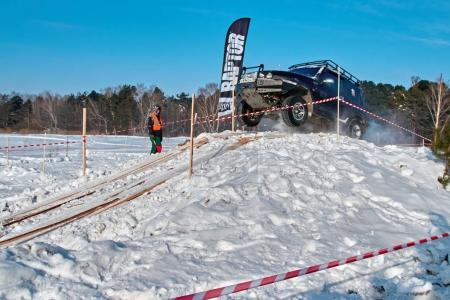 TOMSK, RUSSIA - FEBRUARY 17, 2018: Winter auto show of jeeps - ring race with obstacles, off-road trial. Jumping from jeeps. Car Ssang Yong Korando in jump from springboard. Offroad concept.