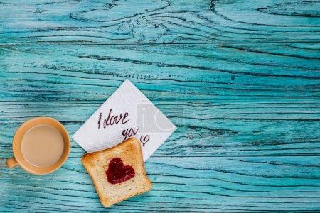 Photo pour Sur un fond en bois, il y a une tasse de café avec un toast sur lequel une confiture sous la forme d'un cœur. Concept de la Saint-Valentin. - image libre de droit