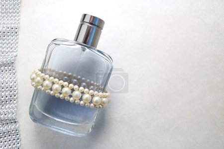 Blue beautiful glass transparent fashionable glamorous bottle of cologne, perfume with white gems and a place for a simple text on a light white background.