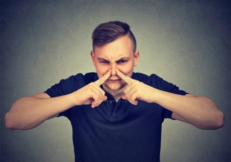 Photo for Man pinches nose with fingers looks with disgust something stinks isolated on gray background. - Royalty Free Image