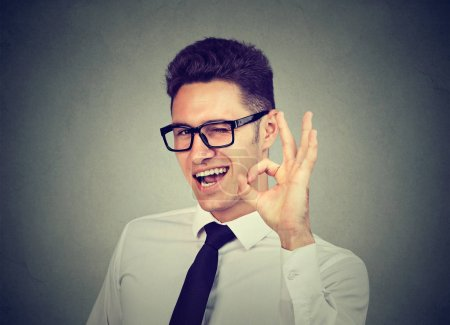 Happy young businessman winking and showing ok sig...