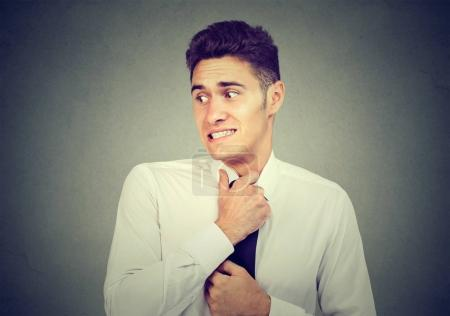Photo for Nervous young man feels awkward looking away anxiously isolated on gray background. - Royalty Free Image