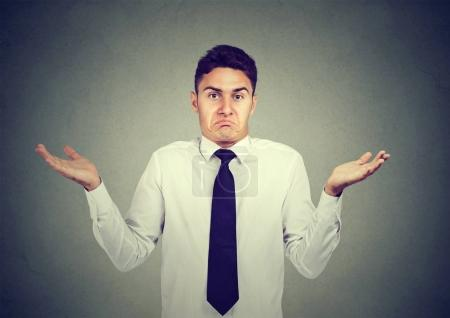 Photo pour Gros plan portrait jeune homme d'affaires haussant les épaules isolé sur fond de mur gris. Langage corporel - image libre de droit
