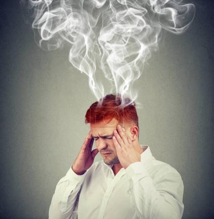 Photo pour Plan conceptuel de l'homme tenant la main sur les tempes et regardant frustré par la fumée sortant de la tête . - image libre de droit