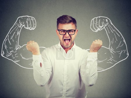 Photo for Young man holding fists up shouting with determination at camera on background of painted strong arms. - Royalty Free Image