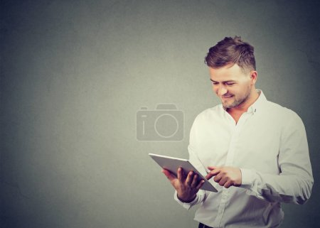 Photo for Content casual guy in white shirt browsing modern tablet enjoying new device standing on gray. - Royalty Free Image