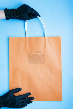 Photo pour Mains dans un gant chirurgical noir tenant un sac en papier. Mesures de précaution de livraison à domicile contre COVID-19 avec amour, Sac cadeau livré sans contact direct . - image libre de droit