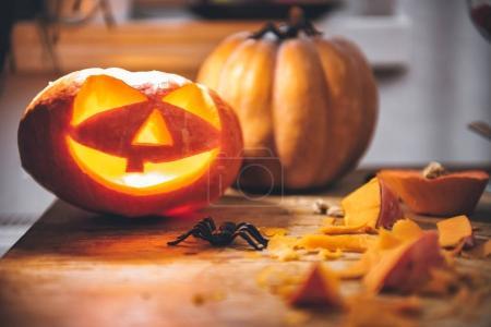 Photo pour Halloween Citrouilles rougeoyantes avec des araignées et des couteaux de cuisine sur la table - image libre de droit