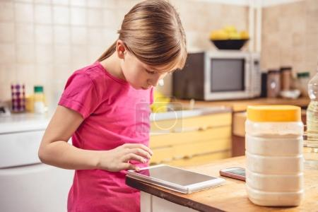 Girl using tablet in kitchen