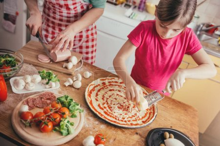 Photo pour Mère et fille cuisine pizza dans la cuisine domestique à la maison - image libre de droit